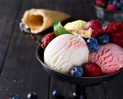 Bowl with ice cream with three different scoops of white, yellow, red colors and waffle cone with frozen berry on dark wooden background , copy space