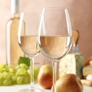 Grape, cheese, pears, glasses and bottle with wine, on white background, copy space