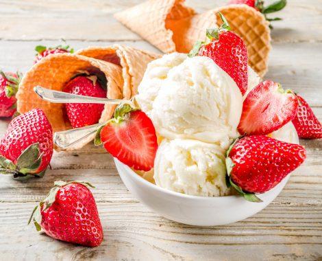 Homemade strawberry vanilla ice cream with fresh strawberries. Sweet berry summer dessert. Wooden background copy space