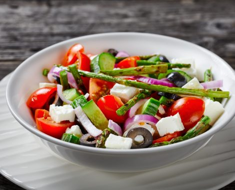 Classic organic vegetables greek salad with grilled asparagus, cherry tomatoes, cucumbers, black olives, red onion rings with olive oil, feta cheese served on a white plate on a wooden table